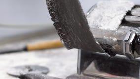 El primer de manos en guantes rueda la pasta negra cruda en máquina de las pastas en la cámara lenta almacen de video