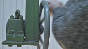 El primer de manos un investigador de sexo masculino gira la rueda manual del mecanismo de apertura de las hojas de la bóveda de  almacen de metraje de vídeo