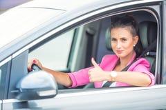 El primer de mostrar de la mano de la mujer los pulgares-para arriba firma hacia fuera con las ventanillas del coche Imágenes de archivo libres de regalías