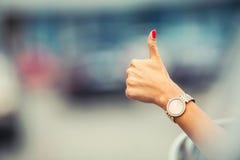 El primer de mostrar de la mano de la mujer los pulgares-para arriba firma hacia fuera con las ventanillas del coche Foto de archivo libre de regalías