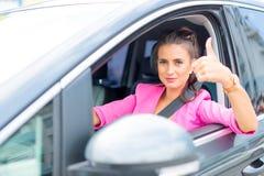 El primer de mostrar de la mano de la mujer los pulgares-para arriba firma hacia fuera con las ventanillas del coche Imagenes de archivo