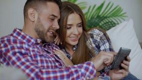 El primer de pares sonrientes jovenes usando la tableta para Internet que practica surf y la charla se sientan en el sofá en sala almacen de metraje de vídeo