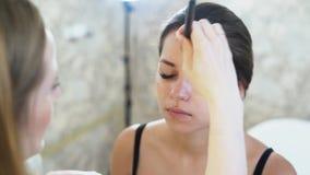 El primer de un artista de maquillaje rubio rubio joven pinta a una muchacha morena joven, aplica un lápiz corrector a su cara co almacen de video