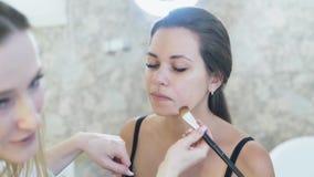 El primer de un artista de maquillaje rubio rubio joven pinta a una muchacha morena joven, aplica un lápiz corrector a su cara co almacen de metraje de vídeo