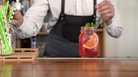 El primer de un camarero joven hermoso da el acabamiento que hace una limonada fresca, fresca del color rojo almacen de video