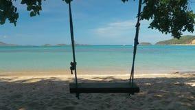 El primer de un oscilación de la cuerda cuelga en la palmera en una playa hermosa con agua blanca de la arena y de la turquesa Sa almacen de video
