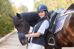 El primer de una chica joven abrazó la cara del ` s del caballo con sus manos Foto de archivo libre de regalías