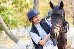 El primer de una chica joven abrazó la cara del ` s del caballo con sus manos Imagenes de archivo