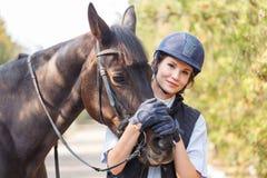 El primer de una chica joven abrazó la cara del ` s del caballo con sus manos Fotografía de archivo libre de regalías