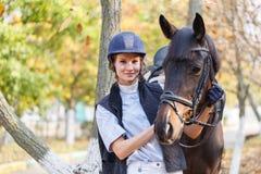 El primer de una chica joven abrazó la cara del ` s del caballo con sus manos Fotos de archivo libres de regalías