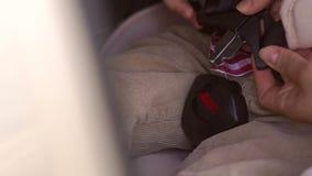 El primer de una madre sujeta sus pequeños cinturones de seguridad del ` s del hijo en asiento de carro en el coche almacen de video