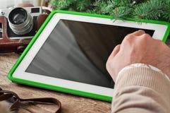 El primer de una mano de los hombres hace clic la tableta de la pantalla en blanco en la tabla de madera Fotos de archivo libres de regalías