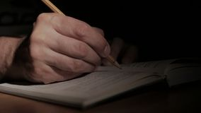 El primer de una mano del ` s del hombre con un libro de papel abierto, escribe una nota con un lápiz en la página almacen de video