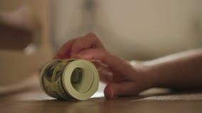 El primer de una mano del ` s de la mujer encuentra y saca de debajo la cama al paquete de billetes de dólar metrajes