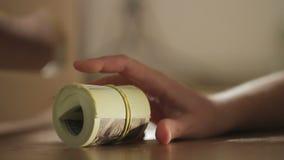 El primer de una mano del ` s de la mujer oculta una pila de billetes de dólar debajo de la cama almacen de video
