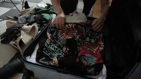 El primer de una mujer recoge suavemente cosas en una maleta almacen de video
