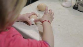 El primer de una niña limpia la cáscara con un huevo hervido del pollo almacen de metraje de vídeo