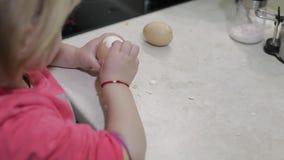 El primer de una niña limpia la cáscara con un huevo hervido del pollo metrajes