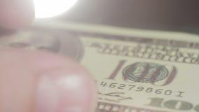 El primer de una persona toma una cuenta del ciento-dólar de la tabla metrajes