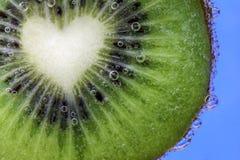 El primer de una rebanada en forma de corazón del kiwi cubierta en agua burbujea imagen de archivo libre de regalías