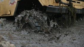 El primer de una rueda de coche se pegó en el agua y el fango sucios La rueda está haciendo girar, pero él desamparado metrajes