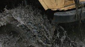El primer de una rueda de coche se pegó en el agua y el fango sucios La rueda está haciendo girar, pero él desamparado almacen de metraje de vídeo