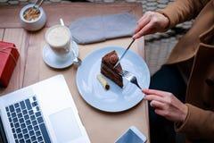 El primer de una tabla con un ordenador portátil, una torta, y un latte, la muchacha está comiendo dispositivos de la torta Visió imagenes de archivo
