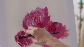 El primer del artista de la muchacha dibuja las flores rosadas en una lona blanca almacen de metraje de vídeo