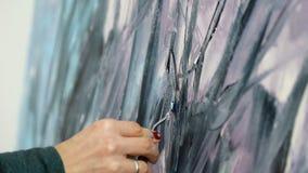El primer del artista dibuja colores negros y oscuros de acrílico en la luz caliente Dibujo con la esp?tula y las pinturas acr?li almacen de metraje de vídeo