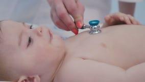 El primer del doctor escucha el bebé con el estetoscopio almacen de video