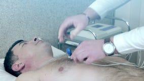 El primer del doctor fija el lechón en el corazón para recibir un electrocardiograma almacen de video