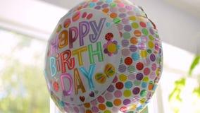 El primer del helio infló el globo con el texto del feliz cumpleaños que reflejaba la luz almacen de metraje de vídeo