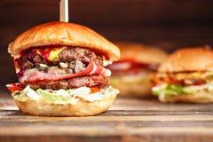 El primer del hogar hizo las hamburguesas sabrosas con carne de vaca, las setas, el tocino, y el queso en la tabla de madera sals imagen de archivo