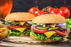 El primer del hogar hizo las hamburguesas sabrosas en la tabla de madera Imagen de archivo