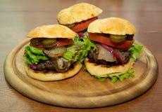 El primer del hogar hizo las hamburguesas sabrosas en la tabla de madera foto de archivo