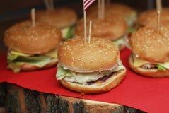 El primer del hogar hizo las hamburguesas sabrosas en la tabla de madera y la servilleta roja fotos de archivo libres de regalías