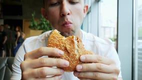 El primer del hombre hambriento joven come la hamburguesa en un café, restaurante de los alimentos de preparación rápida almacen de metraje de vídeo