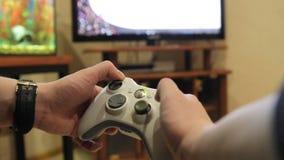 El primer del hombre joven da jugar a los videojuegos en la consola del juego delante de la TV con pantalla grande almacen de metraje de vídeo