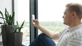 El primer del hombre joven da el SMS que mecanografía que enrolla el teléfono de las imágenes mensaje de texto del hombre que mec metrajes