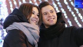 El primer del hombre joven y de la mujer hace un selfie en el teléfono, sonriendo en la noche del Año Nuevo almacen de metraje de vídeo