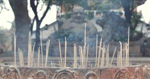 El primer del incienso pega el burning con humo en templo budista almacen de video