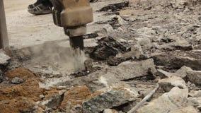 El primer del martillo hidráulico del brazo rompe el asfalto en el camino almacen de video