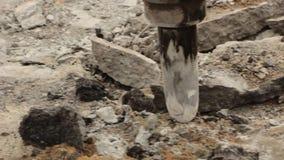 El primer del martillo hidráulico del brazo rompe el asfalto en el camino metrajes