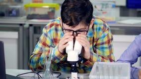El primer del muchacho que mira en el microscopio 4K metrajes