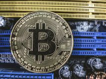 El primer del oro mordi? la moneda, la placa de circuito del ordenador con el procesador del bitcoin y los microchipes Moneda ele fotos de archivo libres de regalías