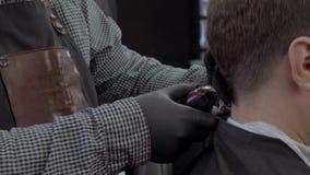 El primer del peluquero corta el pelo por las tijeras en la barber?a Manos del ` s del peluquero en el proceso de trabajo Peluque almacen de metraje de vídeo