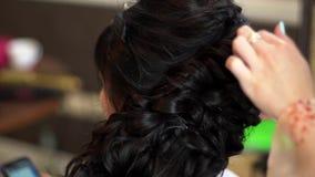 El primer del peluquero profesional da hacer el peinado de la belleza metrajes