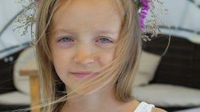 El primer del pequeño blonde elegante huele wildflowers y la sonrisa en la cámara lentamente almacen de metraje de vídeo