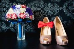 El primer del ramo nupcial de rosas, casandose florece para la ceremonia en la cama en una habitación con los zapatos blancos Foto de archivo libre de regalías