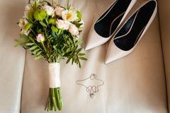 El primer del ramo nupcial de rosas, casandose florece para la ceremonia en la cama en una habitación con los zapatos blancos Imagenes de archivo